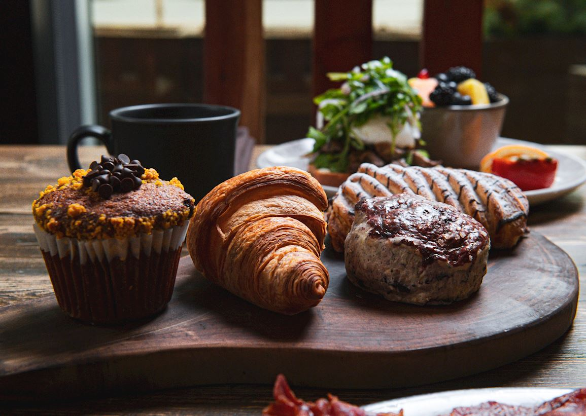 breakfast pastries, bowl of fruit, cup of coffee